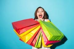 Retrato de una muchacha emocionada feliz que sostiene los panieres coloridos Foto de archivo