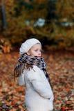 Retrato de una muchacha en el día del frío del parque del otoño Foto de archivo libre de regalías