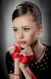 Retrato de una muchacha en estilo retro con la cinta roja Imagenes de archivo