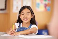 Retrato de una muchacha en la escuela primaria que se sienta en sala de clase Foto de archivo libre de regalías