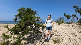 Retrato de una muchacha en la playa de Baikal por un árbol almacen de metraje de vídeo