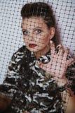 Retrato de una muchacha en ropa del camuflaje a través de la malla Imagen de archivo