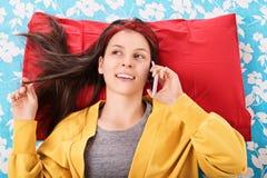 Retrato de una muchacha en su cama que habla en el teléfono Fotografía de archivo