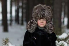 Retrato de una muchacha en un día de invierno escarchado del sombrero y del abrigo de pieles de piel en el bosque Fotografía de archivo libre de regalías