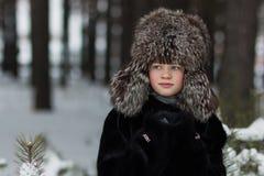 Retrato de una muchacha en un día de invierno escarchado del sombrero y del abrigo de pieles de piel en el bosque Imágenes de archivo libres de regalías