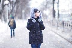 Retrato de una muchacha en un parque nevoso del invierno Fotografía de archivo