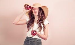 Retrato de una muchacha en un sombrero del verano con la fruta en un fondo coloreado imagen de archivo