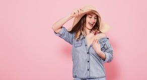 Retrato de una muchacha en un sombrero del verano en un fondo rosado fotografía de archivo libre de regalías