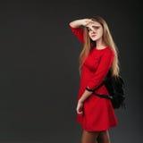 Retrato de una muchacha en un vestido rojo con una mochila de cuero negra Imagen de archivo libre de regalías