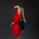 Retrato de una muchacha en un vestido rojo con una mochila de cuero negra Fotos de archivo libres de regalías