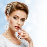 Retrato de una muchacha en un vestido y una joyería blancos en un backg azul Imagenes de archivo
