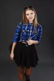 Retrato de una muchacha en una camisa de tela escocesa y una falda negra Imagen de archivo libre de regalías