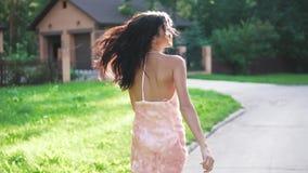 Retrato de una muchacha en vestido de noche Paseos de una mujer joven negligentemente a lo largo de la calle almacen de metraje de vídeo