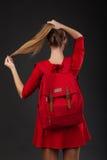 Retrato de una muchacha en vestido rojo, con una mochila roja grande Fotos de archivo libres de regalías