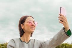 Retrato de una muchacha en vidrios hace el selfie en el teléfono Fondo del cielo azul Imagen de archivo libre de regalías