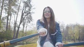Retrato de una muchacha encantadora en vidrios y de una chaqueta del dril de algodón que flota en un barco en un lago o un río La almacen de metraje de vídeo