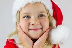Retrato de una muchacha feliz en un casquillo rojo del Año Nuevo Fotos de archivo libres de regalías