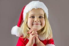 Retrato de una muchacha feliz en un casquillo rojo del Año Nuevo Fotografía de archivo