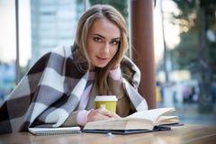 Retrato de una muchacha feliz que se sienta con el libro en café Imagenes de archivo