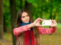 Retrato de una muchacha feliz smilling a la cámara móvil Imágenes de archivo libres de regalías