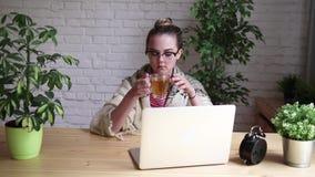 Retrato de una muchacha frustrada que sopla su nariz en un pañuelo mientras que trabaja con un ordenador portátil El concepto de  almacen de metraje de vídeo