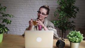 Retrato de una muchacha frustrada que sopla su nariz en un pañuelo mientras que trabaja con un ordenador portátil El concepto de  metrajes