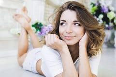 Retrato de una muchacha hermosa apacible, joven lindo, mentira atractiva en el piso, con la presentación del ordenador portátil Foto de archivo libre de regalías