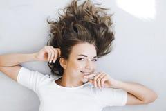 Retrato de una muchacha hermosa apacible, joven lindo, mentira atractiva en el piso, con la presentación del ordenador portátil Fotografía de archivo