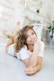 Retrato de una muchacha hermosa apacible, joven lindo, mentira atractiva en el piso, con la presentación del ordenador portátil Imagen de archivo libre de regalías
