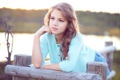 Retrato de una muchacha hermosa, colocándose al aire libre mientras que se inclina en una cerca de madera Imagen de archivo