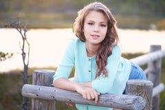 Retrato de una muchacha hermosa, colocándose al aire libre mientras que se inclina en una cerca de madera Imagen de archivo libre de regalías