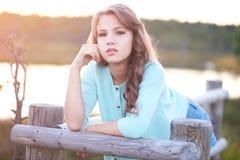 Retrato de una muchacha hermosa, colocándose al aire libre mientras que se inclina en una cerca de madera Fotografía de archivo