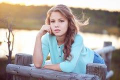 Retrato de una muchacha hermosa, colocándose al aire libre mientras que se inclina en una cerca de madera Imágenes de archivo libres de regalías