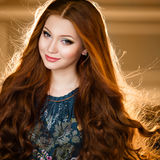 Retrato de una muchacha hermosa con el pelo rojo en un vestido verde detrás imagenes de archivo