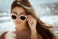 Retrato de una muchacha hermosa con el pelo y las gafas de sol largos Imagenes de archivo