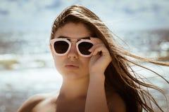 Retrato de una muchacha hermosa con el pelo y las gafas de sol largos Imagen de archivo libre de regalías