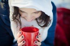 Retrato de una muchacha hermosa con la taza roja en bosque del invierno Imagen de archivo libre de regalías