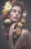 Retrato de una muchacha hermosa con un maquillaje rosado apacible y porciones de flores en su pelo Imagen de la primavera Cara de Foto de archivo libre de regalías