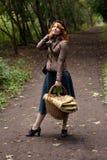 Retrato de una muchacha hermosa del redhair en el parque del otoño. Foto de archivo