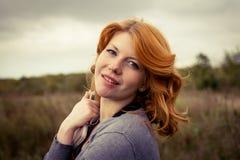 Retrato de una muchacha hermosa del redhair en el parque del otoño. Fotos de archivo libres de regalías