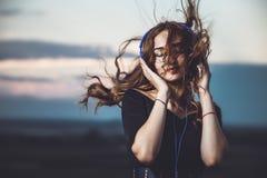Retrato de una muchacha hermosa en auriculares que escucha la música en la naturaleza Foto de archivo