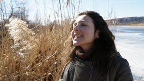 Retrato de una muchacha hermosa en el banco de un río congelado que disfruta de la naturaleza, riendo y jugando con el bastón ama almacen de metraje de vídeo