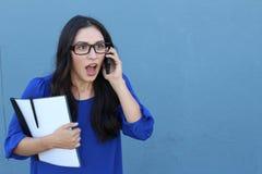 Retrato de una muchacha hermosa en el teléfono mientras que consigue noticias impactantes foto de archivo libre de regalías