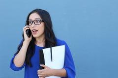 Retrato de una muchacha hermosa en el teléfono mientras que consigue noticias impactantes o asombrosamente Fotografía de archivo libre de regalías