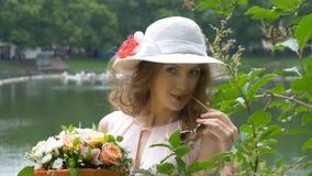 Retrato de una muchacha hermosa en gafas de sol y un sombrero blanco con las flores metrajes