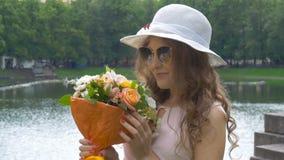 Retrato de una muchacha hermosa en gafas de sol y un sombrero blanco con las flores Primer metrajes