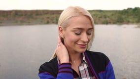 Retrato de una muchacha hermosa en la orilla del río almacen de metraje de vídeo