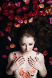Retrato de una muchacha hermosa en pétalos color de rosa Fotos de archivo libres de regalías