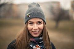 Retrato de una muchacha hermosa en primavera temprana en un casquillo gris imagen de archivo