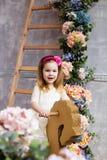 Retrato de una muchacha hermosa en un caballo mecedora de madera en el ro Fotos de archivo